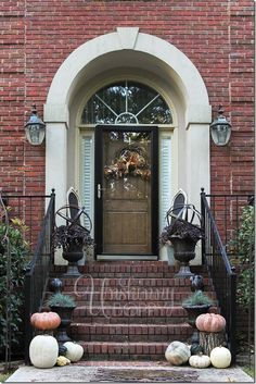 Fall Front porch decorating with pumpkins, urns and metal orbs
