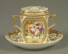 A Derby two-handled chocolate cup, cover and stand, painted with two canted square panels with flower filled baskets on marble ledges, within gilt line rims, reserved on a white ground body elaborately gilt with Regency foliate scrollwork, stand 15.5cm diameter, crown, crossed batons dots and D in orange, circa 1810 (faults)