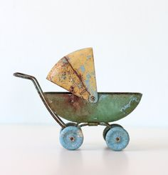 Vintage metal pram.  Nearly everything was made into a toy.  Did anyone have one of these when they were little?