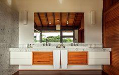 O arquiteto René Fernandes desenhou a bancada de mármore Carrara com duas cubas de sobrepor. O gabinete tem portas de madeira natural e gavetas de laca.