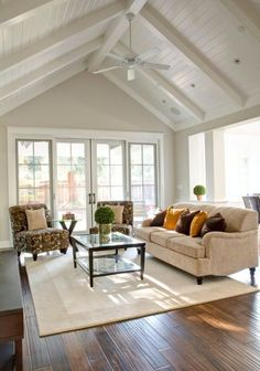 cathedral ceiling living room with white ceiling fan More