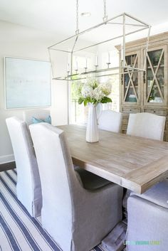 Light and bright dining room with blue and white striped rug, reclaimed wood dining table, linen slipcover dining chairs, Darlana linear pendant, beachy artwork, and fresh limelight hydrangeas. Wall color is Behr Silver Drop.