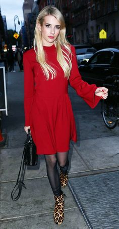 Emma Roberts wears a long-sleeve red mini dress with tights, leopard-print boots, and a mini tote bag