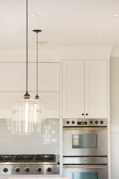 niche modern bell jar pendant lights over a kitchen island in this