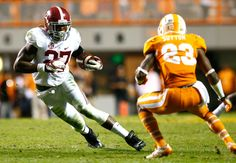Derrick Henry #27 of the Alabama Crimson Tide rushes against Cameron Sutton #23 of the Tennessee Volunteers at Neyland Stadium on October 25, 2014 in Knoxville, Tennessee.