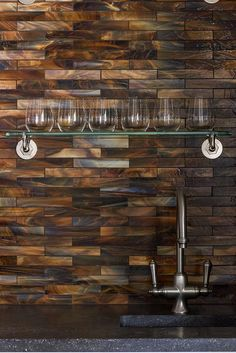 Living room bar nook is filled with a sink under a shimmery copper mosaic tiled backsplash lined with stacked glass shelves.