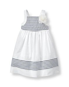 Light and lovely, our poplin dress features a striped top and hem border for nautical charm. 3D blossom accent and permanent back bow finish the celebration style.