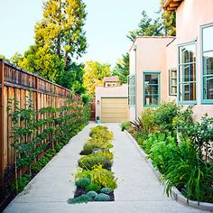 For properties with limited space, this design makes use of the strip down the centre of the driveway with a low-growing garden. Narrow edges along the fence line can also be maximized by espaliering fruit trees or growing vertically. Under planting along the fence with edibles like parsley, chives, oregano, thyme + lemon balm can provide culinary herbs for the kitchen too. More ideas @ http://themicrogardener.com/design/