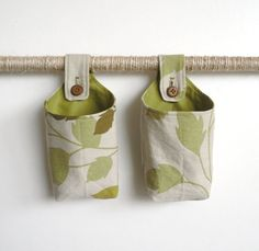 Ever wish your walls had a pocket? These two autumn leaf baskets are the perfect solution! Hang them from any bar fixture, and you have instant wall pockets for all those small items that need a home. Great for holding keys, office supplies, art supplies, bathroom necessities, and so much more! Made from leaf print canvas, and olive green cotton fabrics. These baskets are very sturdy, and machine washable. The hanging loop closes with a vintage wooden button.    Approximately 5 inches wide…