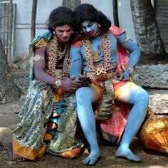 Due uomini nei panni delle divinità indù Lakshman (a sinistra) e Hanuman (R) guardano insieme un video su un telefonino, durante le celebrazioni di Rama Navami, presso un tempio di Bangalore, in India