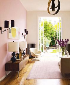 Such a prettily styled narrow space. I adore the pink wall and rug. Love the chair, doors, flowers too.