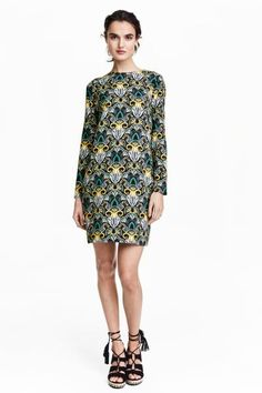 Jurk met dessin: Een korte jurk van zachte, geweven kwaliteit met een geprint dessin. De jurk heeft lange mouwen en een diepe ruguitsnijding met twee blinde knopen. Ongevoerd.