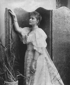 Princesa Alix de Hesse em pé 3/4 à esquerda, ela descansa braço direito no pedestal. Ventoinha em sua mão esquerda. Vestido de manga curta com decote baixo, jóias. A fotografia está assinada: 'Alix 1894' 'You very loving'.