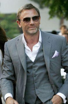 Daniel Craig fuera de personaje luce impecable en un traje gris pólvora. La falta de corbata y la camisa relajada permite crear un look muy accesible y semi formal