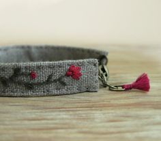 Braccialetto bracciale floreale - fiori rosa e una mano di vite grigio scuro ricamato su lino grigio