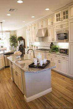 I like the side counter with dishwasher placement.  functional and cute...  antique white kitchen cabinets with light grey and white granite but I would do dark laminate wood floors. I am not of fan of that color for wood floors