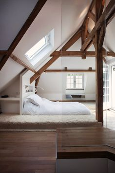 A platform bed is tucked into the eaves of an attic with exposed beams. [1024 x 1536]