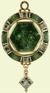 Gold, Colombian emerald, enamel, diamonds, woven material, possibly hair, behind the emerald. Purchased by Queen Mary.  Large table-cut hexagonal emerald, set and backed in gold; surrounded by a frame with white, black, blue, green and red champlevé; enamel cartouches with rosettes alternating with six table-cut diamonds.