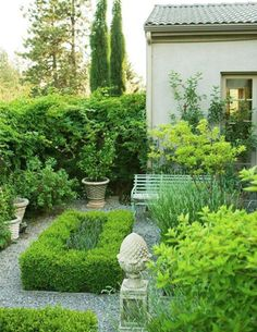 Boxwoods, pea gravel and a perfect bench.  Better Homes and Gardens.