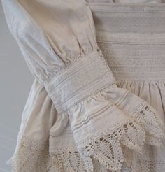 Croatian folk costume - white smocking, white embroidery. Smocking on dress sleeve, and at top of apron, just below waistband.