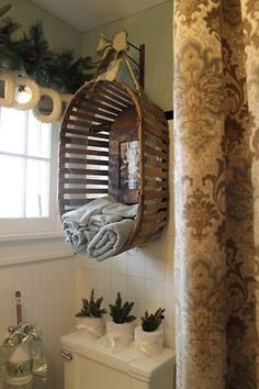 Upcycle an old wooden basket into a bathroom towel holder. I think I would find one a tad smaller though.