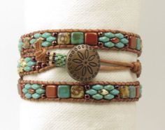 A stylish Bohemian bracelet. Its beaded with the popular SuperDuos, Czechmate Tiles, and Silky beads which are pressed glass beads made in the Czech Republic. The beads are pastel emerald, crystal bronze fire red, silver, and dark bronze. Fire polish beads of the same colors are interspersed. They have all been stitched onto 1.5mm natural dark brown leather that is FREE OF LEAD, AZO'S, PCP, MERCURY, FORMALDEHYDE, CHROMIUM VI, CADMIUM AND OTHER CARCINOGENIC/HAZARDOUS CHEMICALS and is…