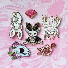 Pretty and perilous  . . . [Image description: 6 enamel pins arranged on pink marbled paper. The pins are a gem by @lizharrydesign  a bat by @juicette  a mousemoth by @minnowandmoss  a spider cat by @gildedcreaturesart  a bat skull with flowers by @monstermaker  and a flower by @britsketch ] . . .