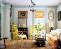 A great mix of pieces here with yellow accent chairs, a campaign chest, trunk coffee table, sofa and lantern