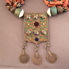 Silver, enamel, amazonite, coral, shells, glass… Morocco     Description     The enamelled amulets (Herz) are worn by the Jewish women of the Anti-atlas and are often mounted on multi- stones necklaces … these amulet are supposed to protect those who wear them against the bad fate…      Weight:287,4gr    Height:Pend : 4,7inch x 2,20inch    Lenght:21,65