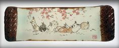 Rabbits lounge under a seasonal canopy of plum blossoms marking the end of Winter on this stoneware appetizer tray with textured bamboo handles. By Tracie Griffith Tso of Reston, Va.