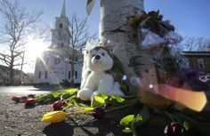 Flowers and stuffed animals of a makeshift memorial for school shooting victims encircle the flagpole at the town center in Newtown, Conn., Saturday, Dec. 15, 2012