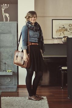 Flannel scarf, denim shirt, belted black skirt, brown leather shoes.
