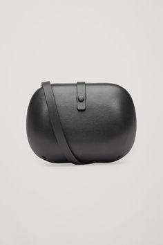 This hard case shoulder bag is made from soft leather with a matte finish. A minimal design, it has a single lined main compartment, a small inside pocket and is closed with a leather strap with a magnetic push button.