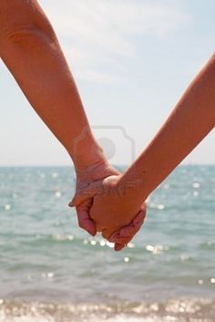 Mother and daughter holding hands near the beach Stock Photo. Great idea for brother sister.