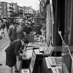 Street market, Portobello Road, Kensington, London, 1962-1964. View along Portobello Road showing stalls outside shops. A woman bending over a stall selling prints can be seen in the foreground.