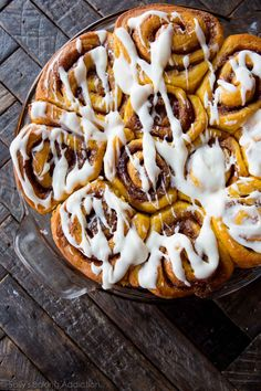 Soft pumpkin cinnamon rolls filled with a gooey cinnamon swirl and topped with maple cream cheese icing! Recipe on sallysbakingaddiction.com