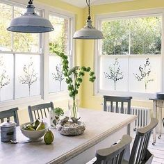 breakfast room; traditional table w/metal (?) chairs; industrial pendants; white floors; yellow walls