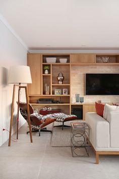 Decoração de apartamento integrado e com crianças. Sofá de madeira estofado com almofadas em cores, obras de arte, jardim vertical e tapete, poltrona, luminária de chão e estante com nichos de madeira.