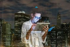 Young woman using digital tablet at home against city lights by Simone Becchetti