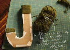 How to make cardboard letters and wrap them in yarn. Ahhh, use double-sided tape in the tricky parts. Would have been useful as I struggled thru the M in our family room. Better idea than whipping out the glue gun!