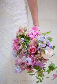 Brides.com: The Most Pin-Worthy Real Wedding Details of the Week: May 16, 2014. Florist Blossom and Branch created a bright bouquet filled with peonies, lisianthus, sweet peas, and garden roses to fit a Gatsby-inspired garden wedding. Cascading vines add a romantic touch to the otherwise classic blooms.  See more photos from Laura and David's Gatsby-inspired Long Island, New York wedding here.