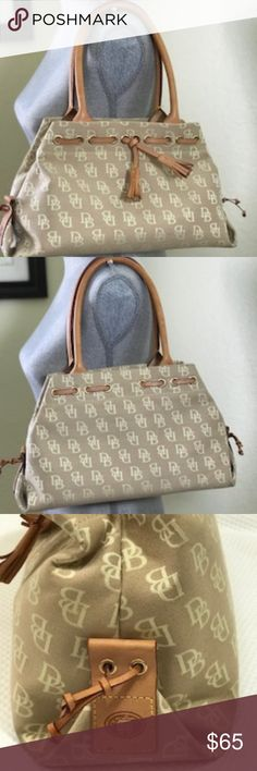 Dooney & Bouke Handbag in Leather and Cloth Pre-loved Classic Tan Monogram Tote. Gorgeus Leather handles and Tassel.  Ink stain inside and one small stain on the back, otherwise it is in excellent condition. No stains on the bottom of the purse. Dooney & Bourke Bags Totes