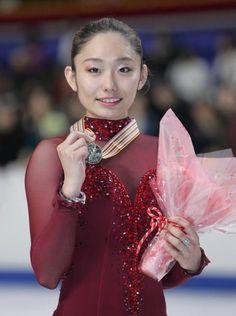 19歳の安藤が頂点に―。2007年3月24日に東京体育館で行われたフィギュアスケート世界選手権最終日の女子で、安藤美姫(トヨタ自動車)が合計195.09点で金メダル、初出場の浅田真央(愛知・中京大中京高)は合計194.45点で銀メダルを獲得した。安藤は日本女子で3大会ぶり、史上4人目の世界女王。日本女子の1、2位独占は史上初の快挙となった。  ショートプログラム(SP)2位の安藤は、この日のフリーで注目の4回転ジャンプには挑まなかったが、ジャンプや表現力で高得点を出し、フリー2位で逆転勝ちした。  写真は、金メダルを手に笑顔の安藤美姫 【時事通信社】