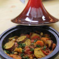 Vegetable Tagine Recipe - Vegetables cut in circles are mixed in with dry spice mix, lemons, chick peas, coriander leaves and parsley. Served with cous cous.