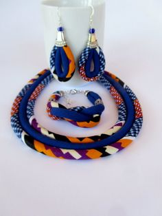 Lovely cobalt blue African fabric jewelry set that I made using African wax material and added a plain blue cotton fabric.I have also added a lovely twisted knot to the bracelet with two filigree beads . The cords are binned together with gold silver cups and chain All hand made and designed by me. This set as all my fabric necklaces is very light and one feels almost no weight on the neck or earrings. Please choose your choice of set by the drop down menu length of the necklace from one…