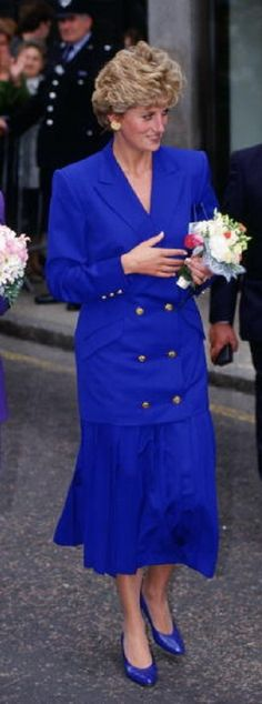 Princess Diana, I think this is the photo with her walking with her sister Sarah Mccorquodale. Yes is so. This: September 09, 1992 Diana, Princess of Wales with her sister and Lady-in-Waiting, Sarah McCorquodale (a Getty Image).. Princess Diana in an electric blue suit, pleated maxi skirt, double-breasted jacket gold buttons.