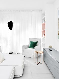 Reading nook in living room with hidden color and metallic rose gold side table, modern floor lamp, and green pillows