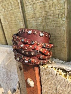 """Beautiful hand crafted cuff - made by The Rowdy Cowgirl... Excellent craftsmanship!   The gunslinger bracelet is a wide cuff that wraps uniquely around the wrist and is designed to fit tight. The gunslingers of the old west wore a leather cuff to keep their shirtsleeves from getting in the way. A hot new twist on an old style!   Extra Long Leather Gunslinger Cuff   Swarovski Crystals, Metal Studs   Beautiful Tooled Leather   Adjustable two snap closure   Will fit a 7 1/4"""" to 8&quo..."""