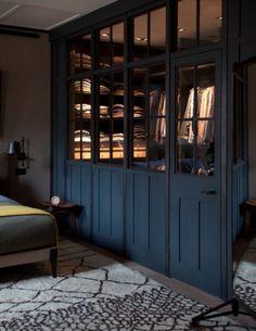 Closet behind glass doors in bedroom