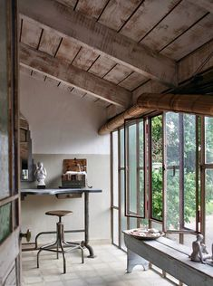 rustic summer house with a patio and french windows | simple wooden industrial furniture lends a modern feel | tonal colour palette - the perfect weekend escape